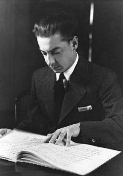 Herbert von Karajan liest aus einem Notenbuch