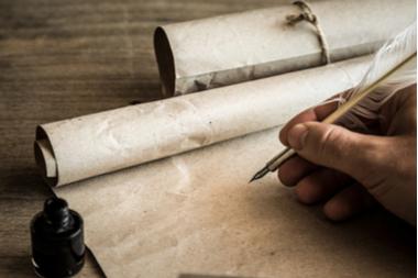 Mann schreibt mit Feder auf Papyrus
