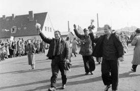Dei Heimkehrer vom Krieg kommen winkend zurück ins Friedland