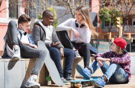 Jugendliche sitzen vor der Schule und unterhalten sich